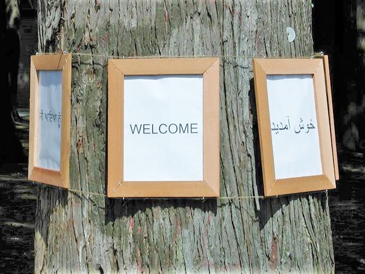 As part of their successful effort to turn a problem property into a vibrant bumping place, Newton neighbors in Surrey, BC hung welcome signs in all the languages of their diverse community.
